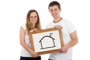 happy couple holding a picture of a home