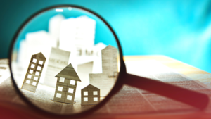 magnifying glass over paper houses